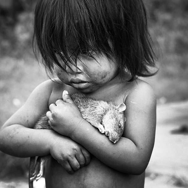 Một bé gái người Guarani đang ôm chặt 1 chú chuột chết